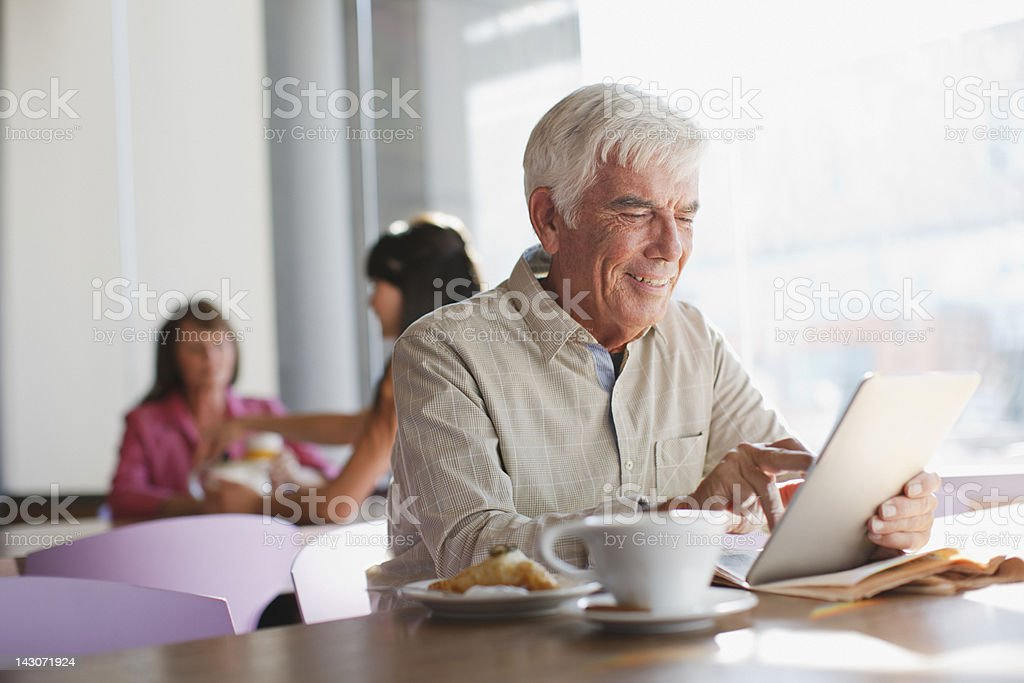 Older man using tablet computer in cafe royalty-free stock photo