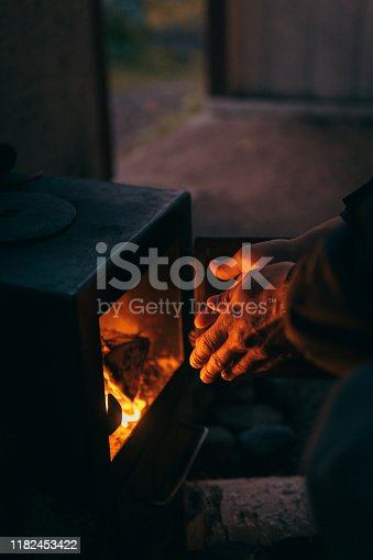 Older man warms his hands by the stove. Rago National Park, Norway