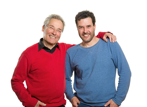 Older man wearing red and holding younger man wearing blue stock photo