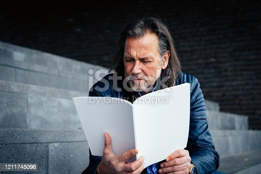 Older man with beard and long grey hair sits on a staircase and reads a magazine with a blank cover.
