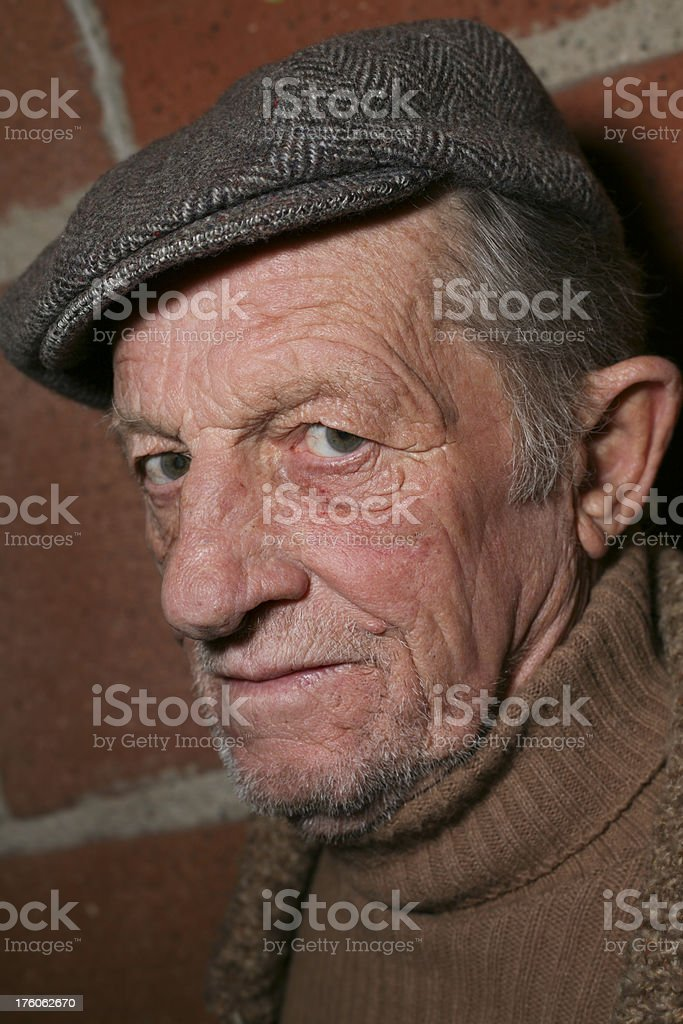 Older Man with Hat Next to Brick Wall stock photo