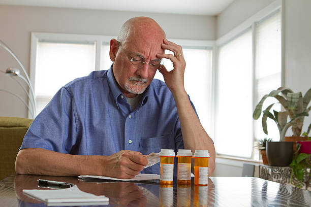 Older man with prescription medications Older man with prescription bottles, horizontal expense stock pictures, royalty-free photos & images
