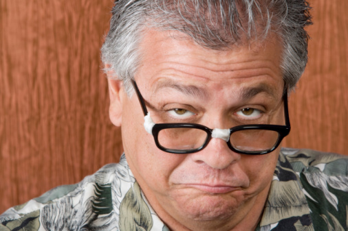 Older man with taped glasses making a funny face