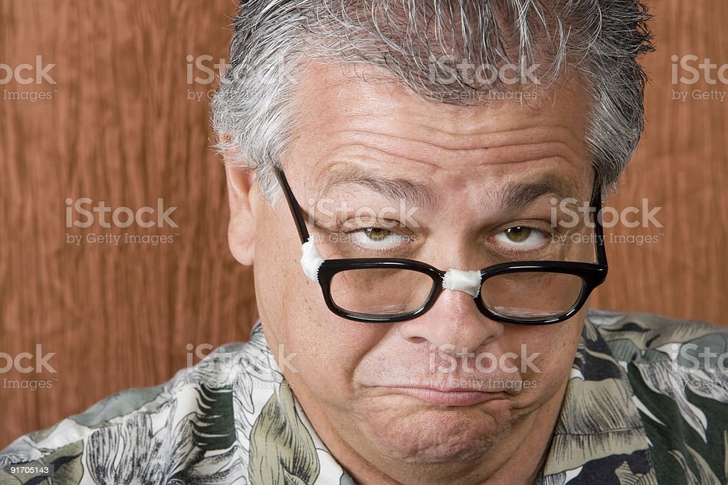 Older man with taped glasses making a funny face stock photo