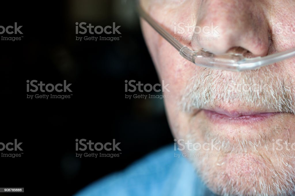 Older man's face with oxygen cannula being used stock photo