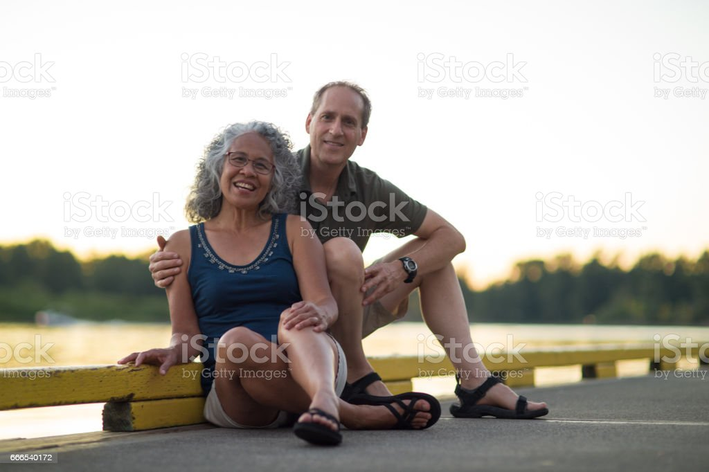 Older mature couple poses on dock after kayaking stock photo