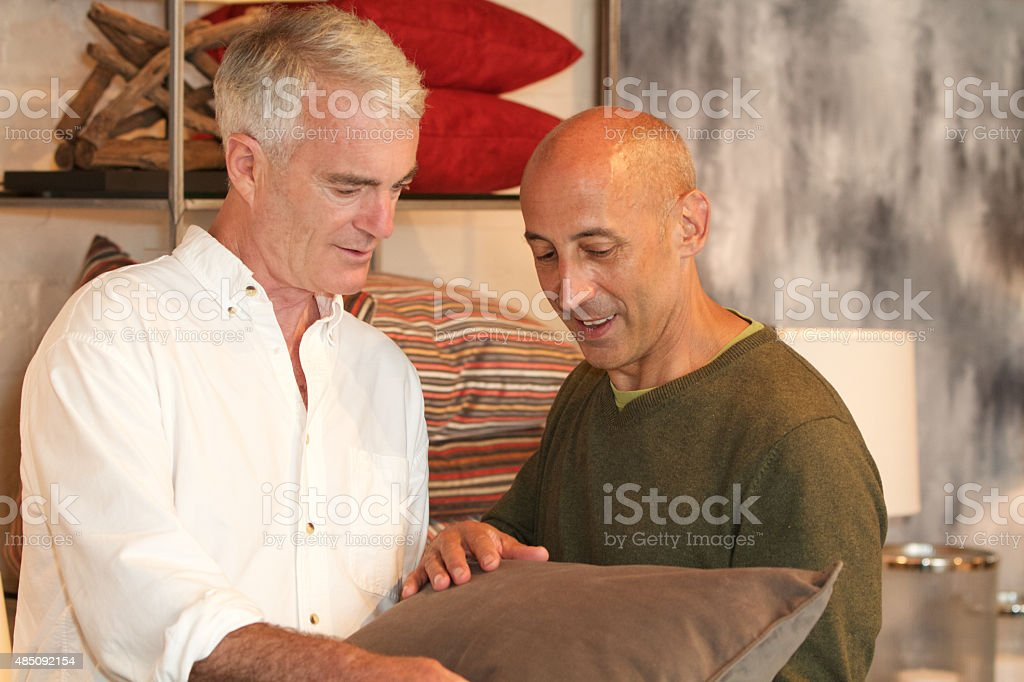Older, mature, senior gay male couple shopping for pillows/furniture stock photo