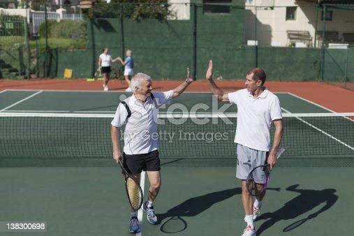 670054434istockphoto Older men high-fiving on tennis court 138300698