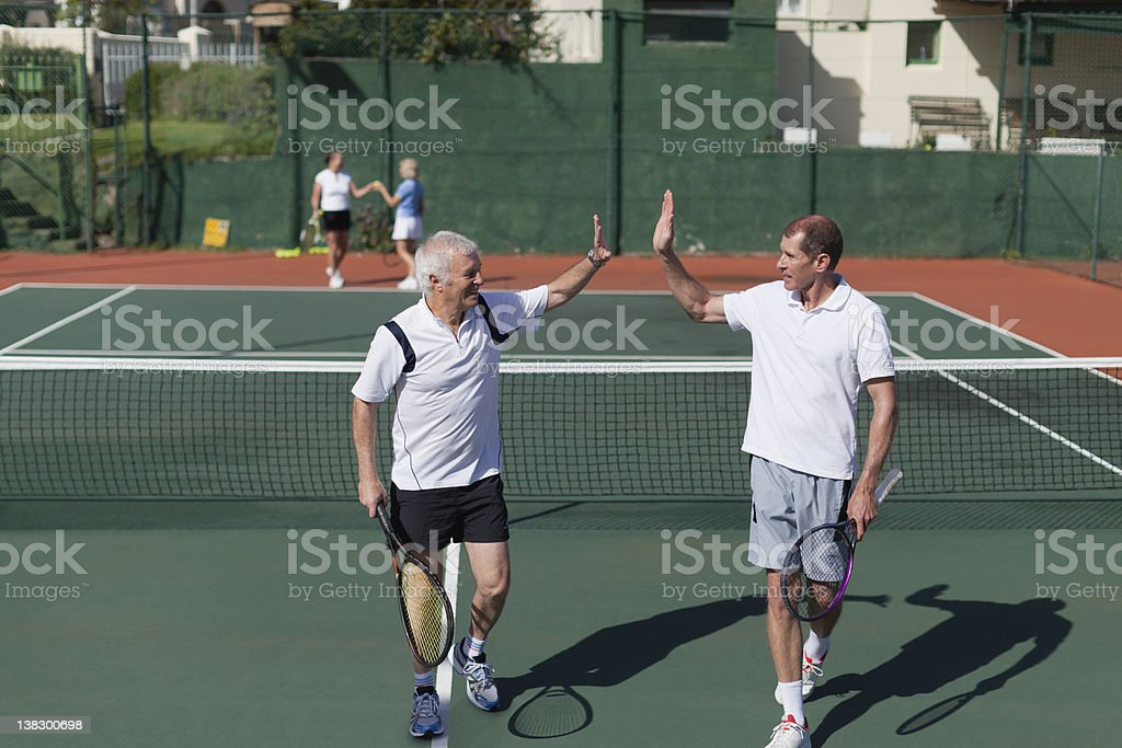Older men high-fiving on tennis court stock photo