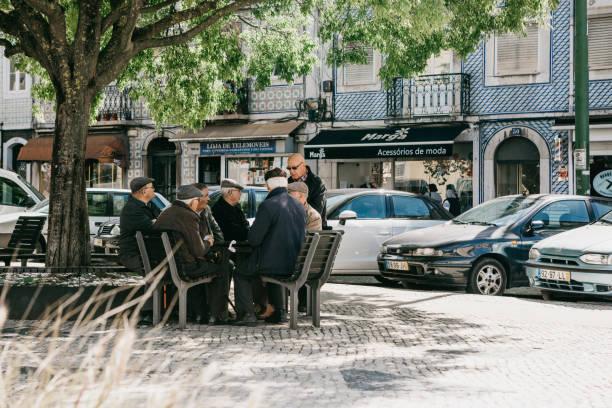 older men locals sit on a bench and communicate in lisbon in portugal - people lisbon imagens e fotografias de stock