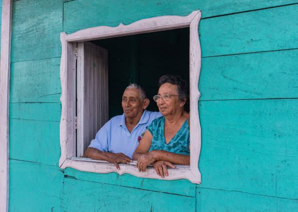 older Mexican couple looking out of window stock photo