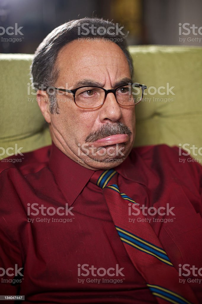 Older Middle Aged Man Seated Makes a Funny Face stock photo