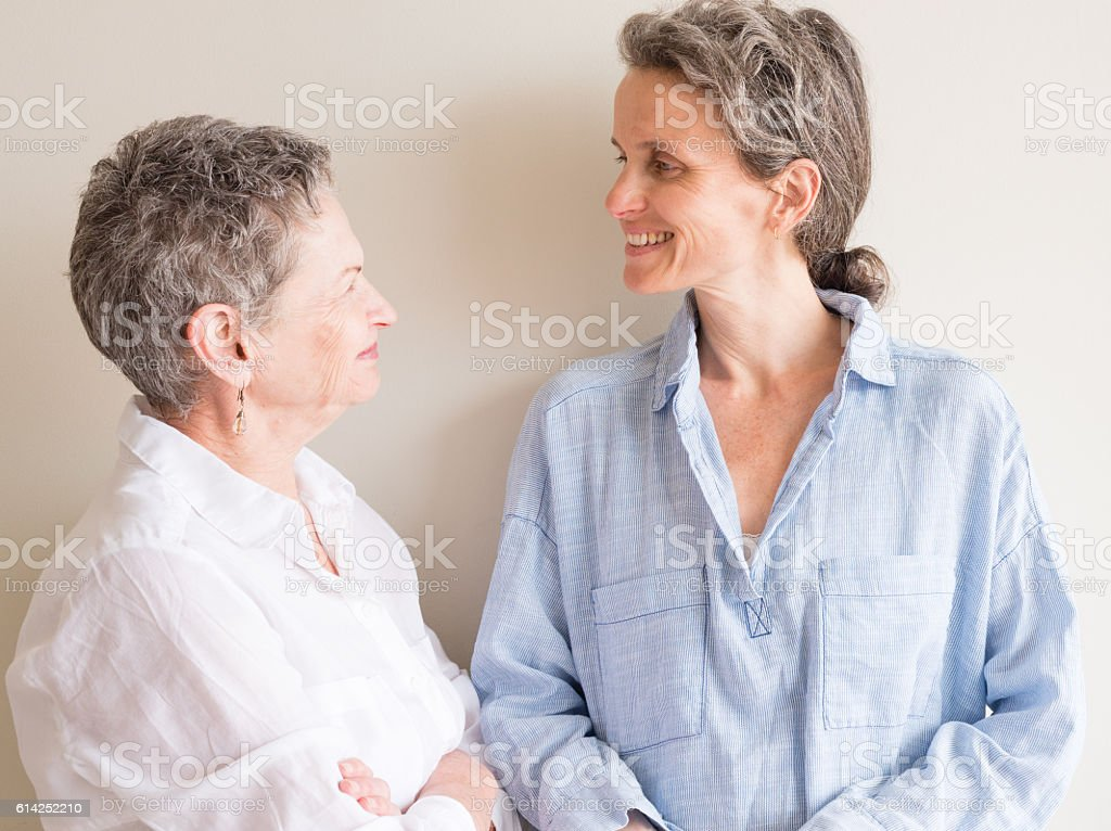 Older mother and daughter smiling stock photo