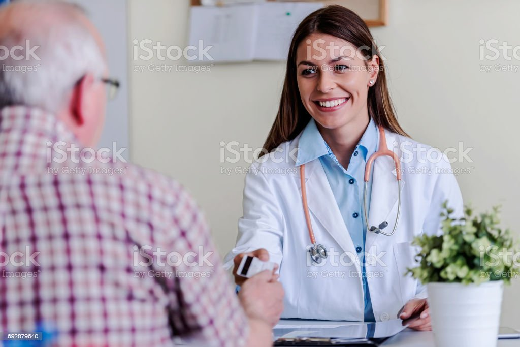 Older patient at woman doctors office paying exam with credit card stock photo