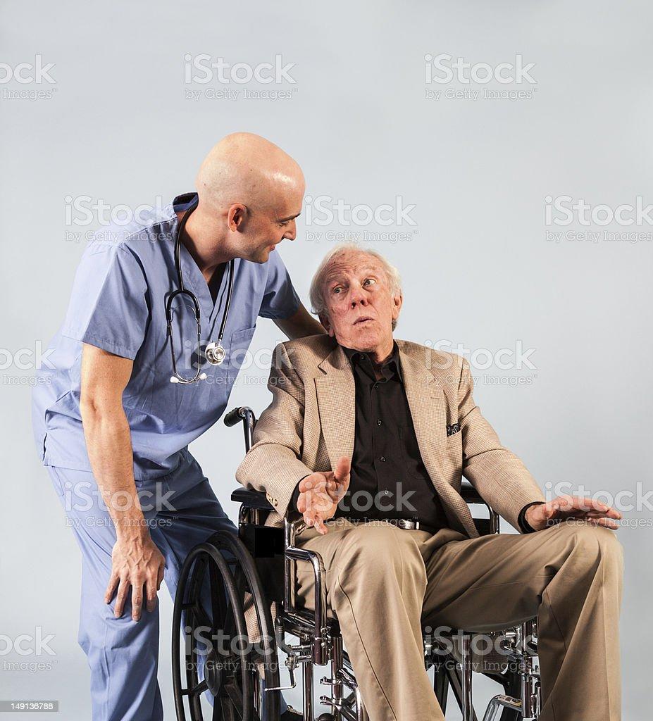 Older Patient Speaks with Male Nurse stock photo