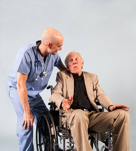 older patient speaks with male nurse - carolinemaryan stock pictures, royalty-free photos & images