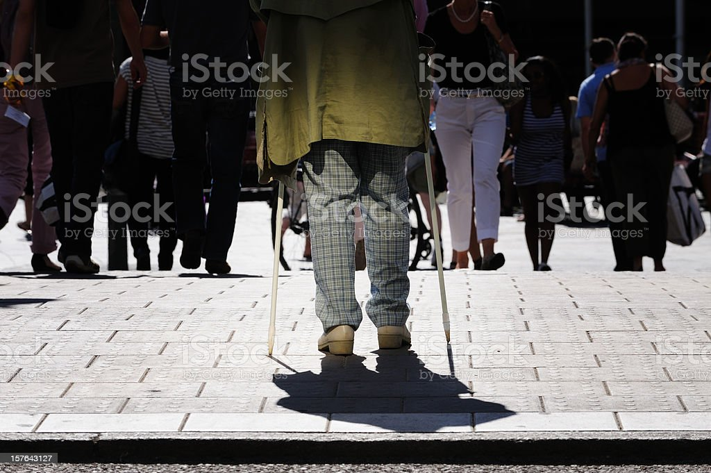 Older person with walking poles, next to zebra crossing royalty-free stock photo