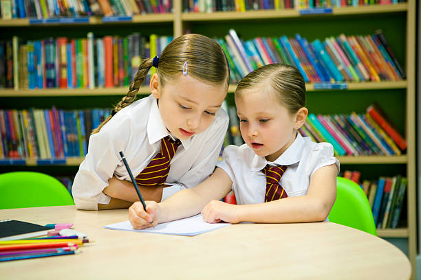 Older pupil helps this younger student with her writing stock photo