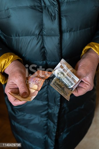 Older senior woman holds EURO banknotes - Eastern European salary pension - After brexit