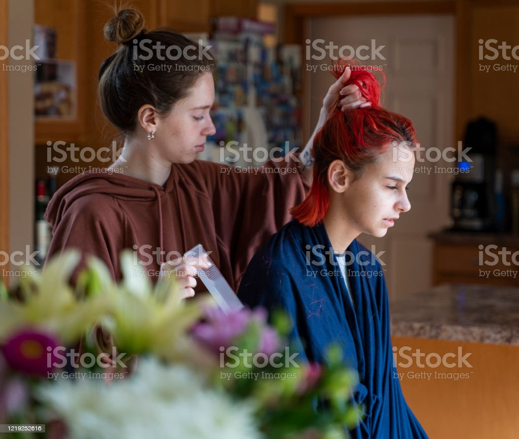 Older Sister Cutting Her Younger Sisters Hair In The Kitchen Stock