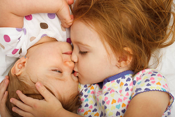 Older sister kissing baby in bed stock photo