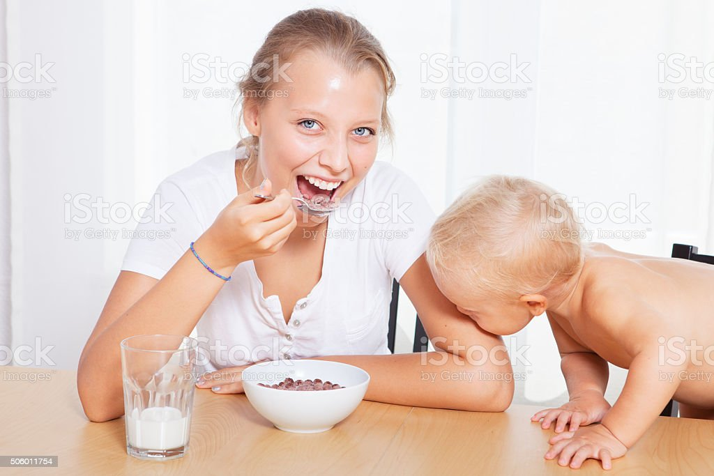 Older sister with her little brother sitting at the breakfast stock photo
