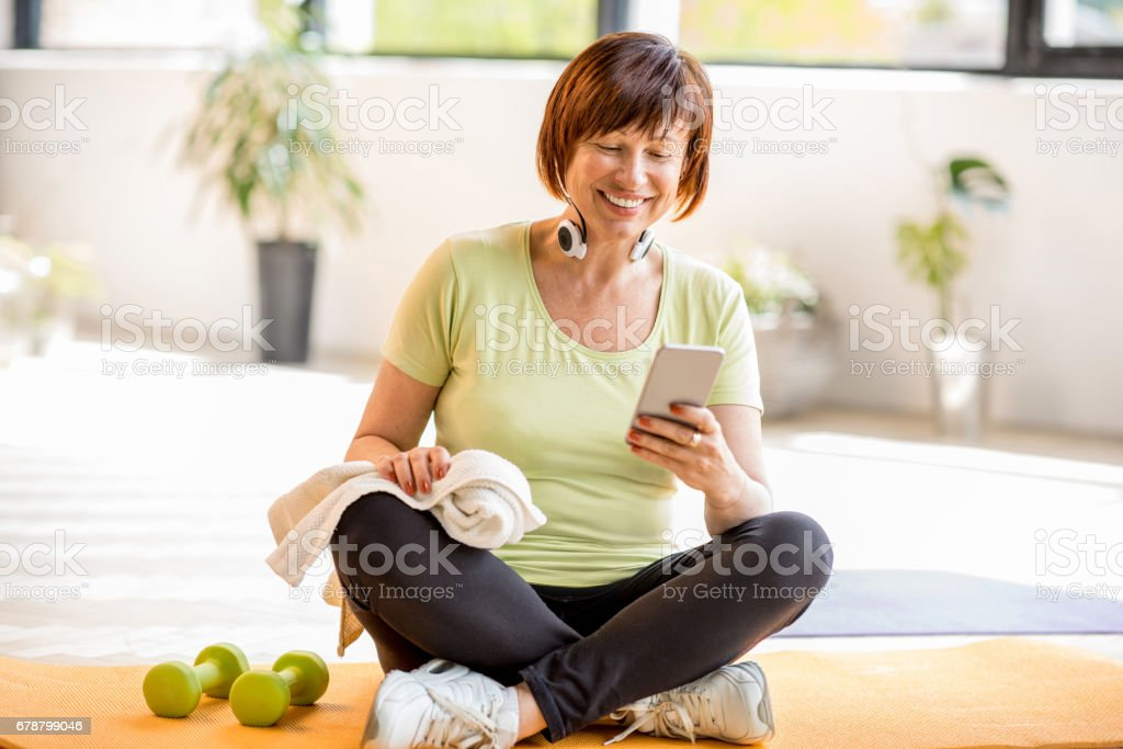 Older sports woman with smartphone indoors stock photo