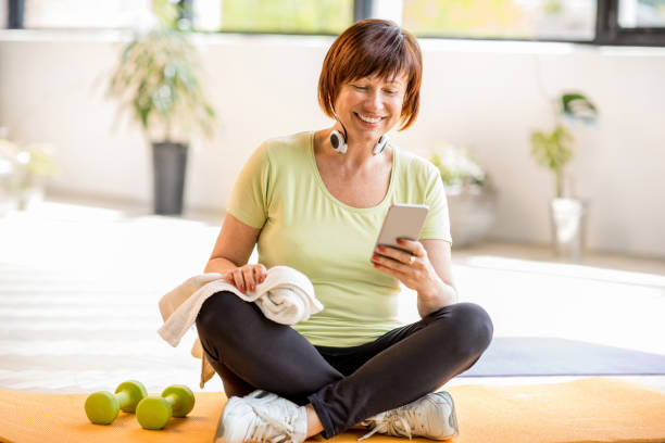 older sports woman with smartphone indoors - older woman phone stock photos and pictures