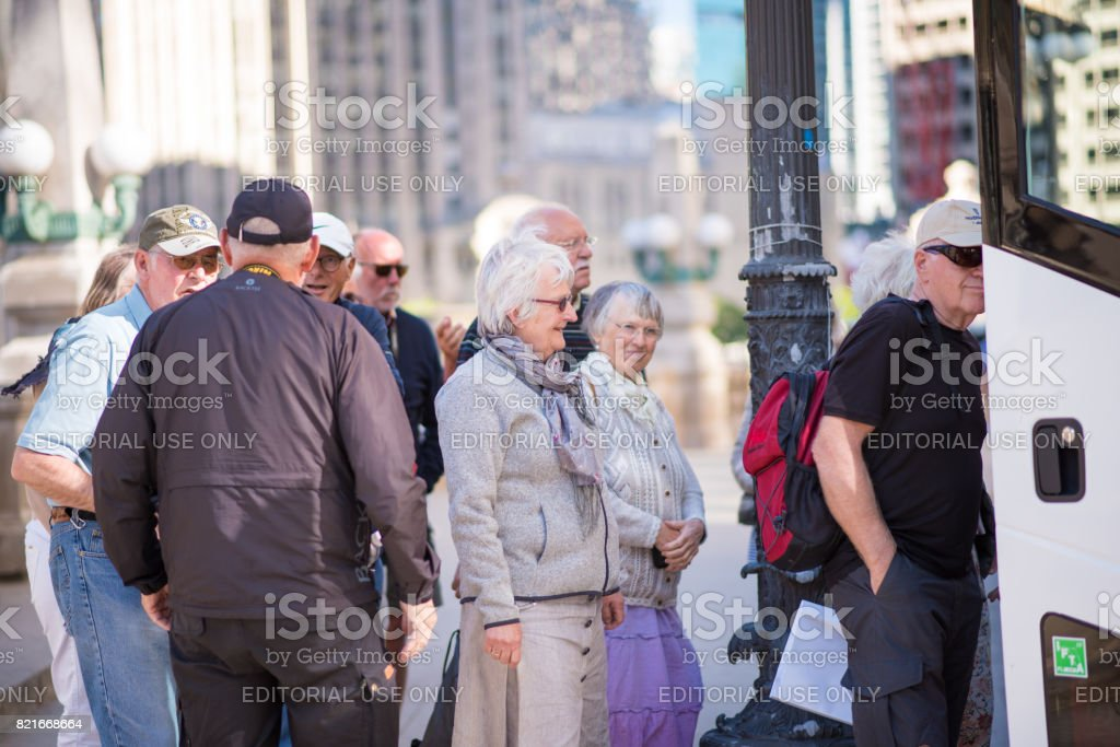 Older tourists exploring Chicago by bus stock photo