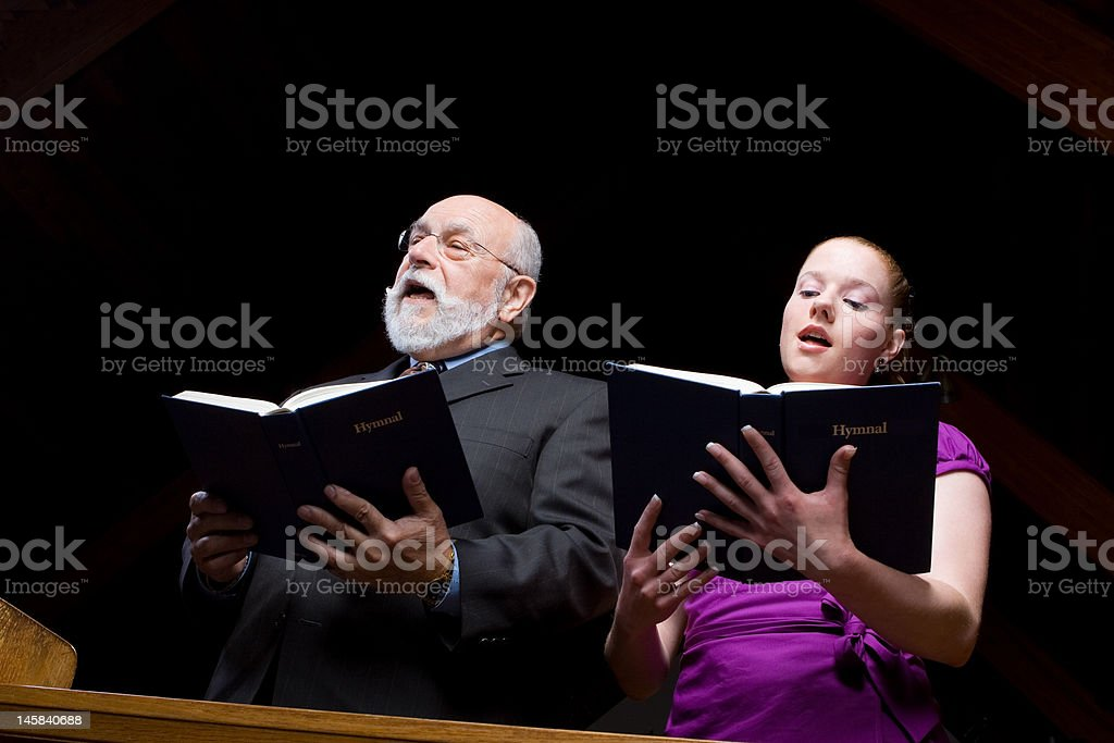 Older White Man Young Woman Singing in Church Holding Hymnals royalty-free stock photo
