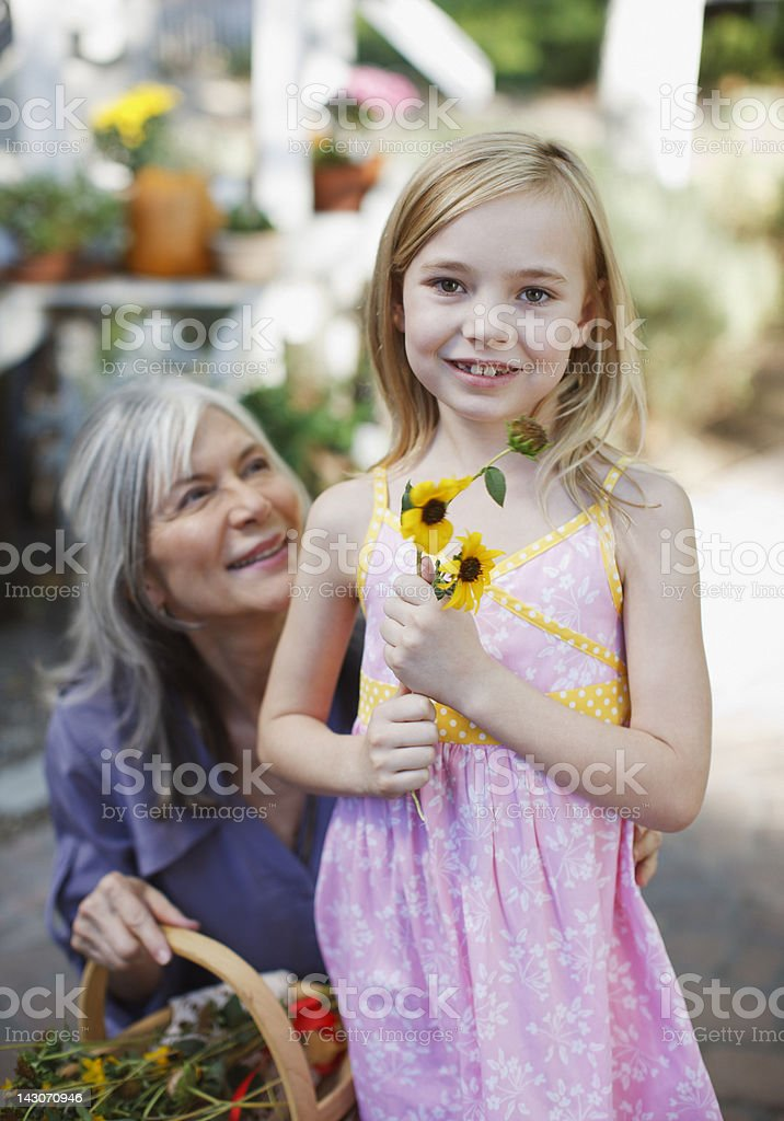 Older woman and granddaughter picking flowers royalty-free stock photo