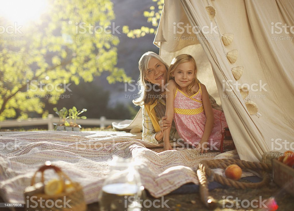 Older woman and granddaughter sitting in tent stock photo