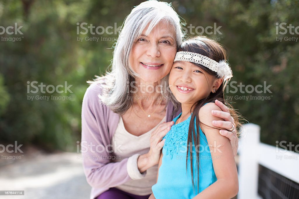 Older woman and granddaughter smiling together royalty-free stock photo