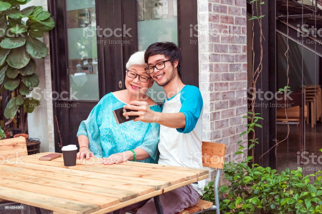 Older woman and young man taking selfie royalty-free stock photo
