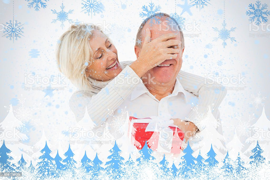 Older woman covering her partners eye while holding present stock photo