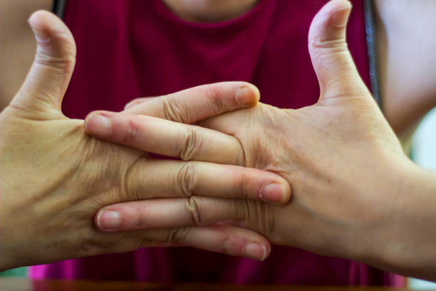 older woman cracking their knuckles - knuckle stock photos and pictures
