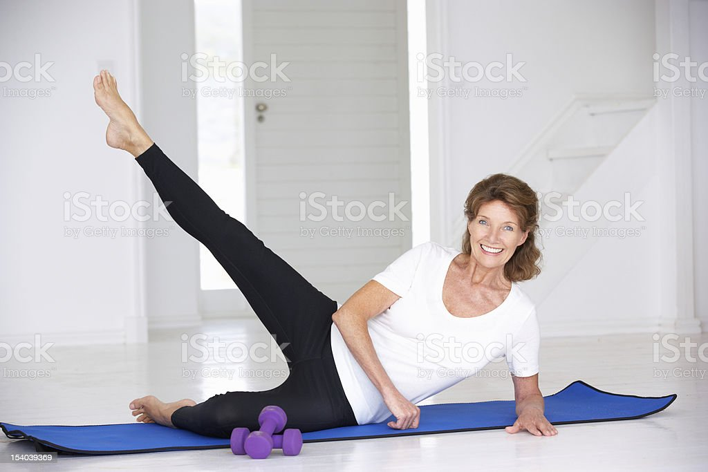 Older woman exercising on a yoga mat with weights nearby stock photo