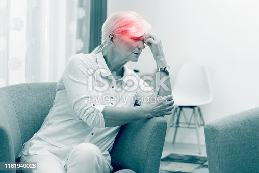 Older woman has a headache. Pain, red point effect. Senior healthcare concept