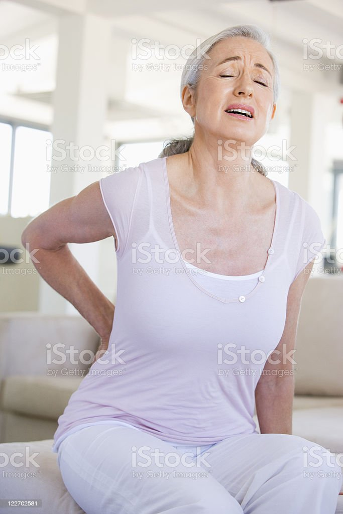 Older woman holding her back with pained expression royalty-free stock photo