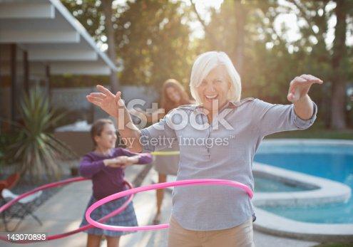 istock Older woman hula hooping in backyard 143070893