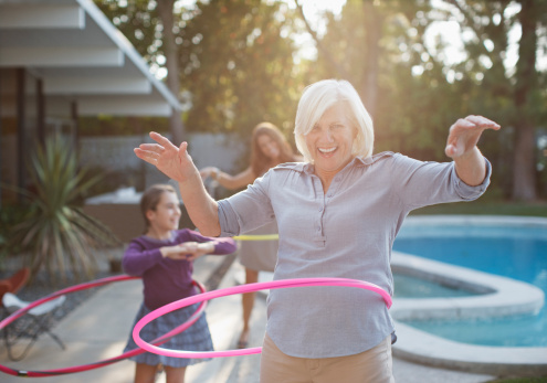 istock Older woman hula hooping in backyard 143070893
