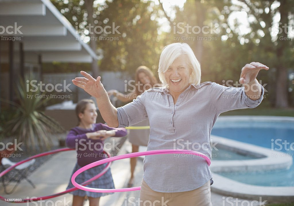 Older woman hula hooping in backyard stock photo