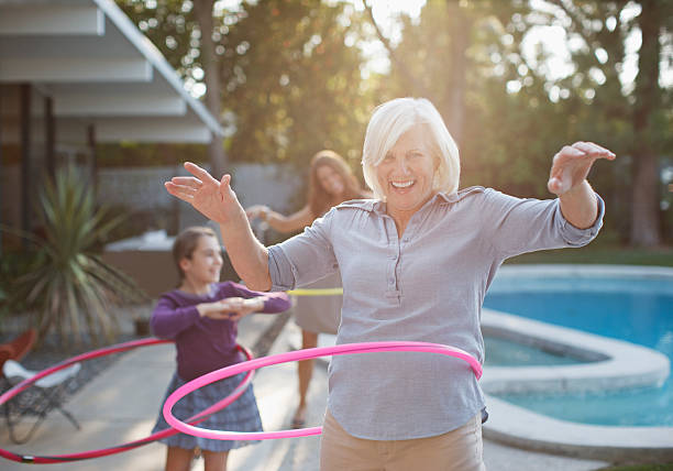 older woman hula hooping in backyard - activiteit bewegen stockfoto's en -beelden