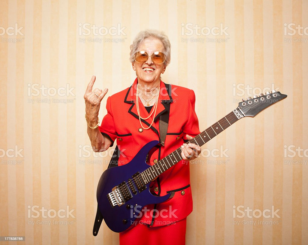 Older woman in a red suit and with an electric guitar stock photo