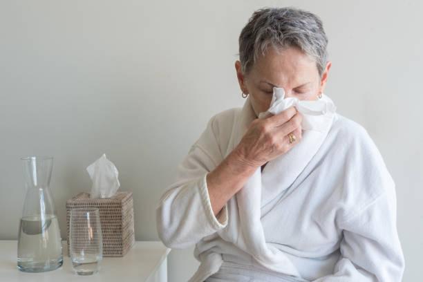 Ältere Frau im Bademantel Nase weht – Foto