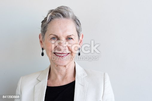 Head and shoulders view of beautiful older woman with short grey hair and beige jacket against neutral background (selective focus)