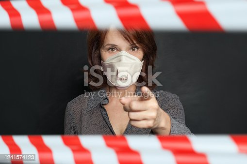 Older woman in protective mask pointing on blackboard background