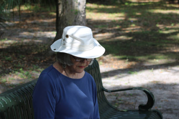 Older woman in wooded park stock photo