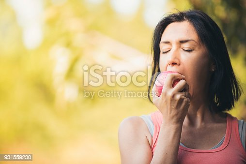 istock Older woman is eating apple after exercising to take care of their health.Eat healthy eating concept. 931559230