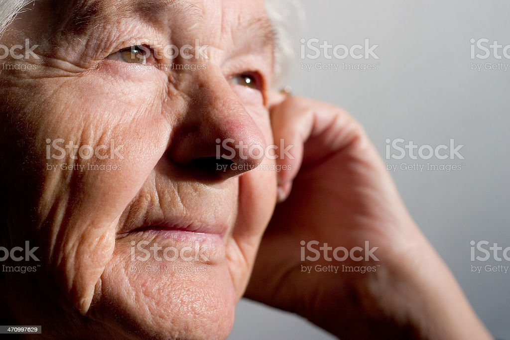 Older woman leans head on hand and gazes into distance royalty-free stock photo